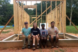 Students in front of the framework of Dave's Revised Home